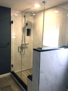 Custom tiled shower with Linear Drain to accommodate large format tile. 12 x 24 Carrara Wall Tile, with Linden Point Grigio Floor tile  on main bath and in shower. Threshold, Seat Bench, and 1/2 wall cap are Blue Pearl, custom Granite.