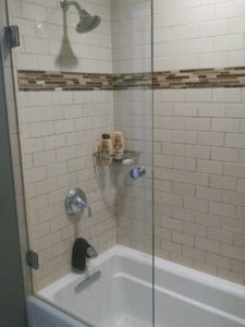 Subway Tile with a Sharma Tub with additional upgrades of glass listello and glass door