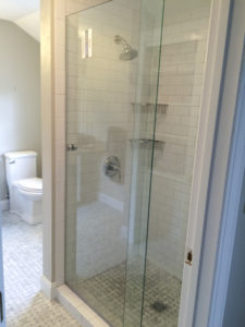 Subway tile with Frameless pivot door (upgrade) and an additional basket (upgrade)